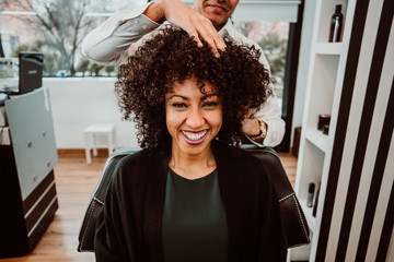 Beautiful latin woman with short curly brown hair getting a treat at the hairdresser. Latin hairdresser working her afro hair. Lifestyle