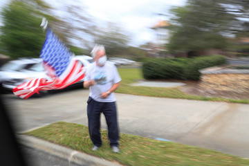 A man wearing a mask waves the U.S. flag as the presidential motorcade passes by, following a private fundraiser, in Longwood