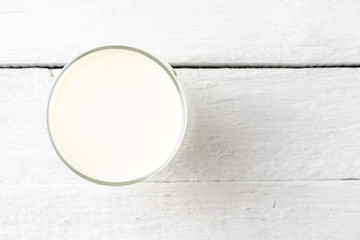 Overhead shot of glass of milk on white wooden table. Close up