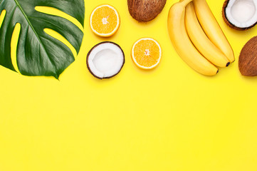 Wall Mural - Summer tropical composition. Green tropical leaves of palm trees and monstera, coconut, orange, bananas on bright yellow background. Flat lay, top view, copy space. Creative background food, fruit