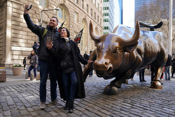 A woman poses for a photo with the Charging Bull statue in the Manhattan borough of New York City
