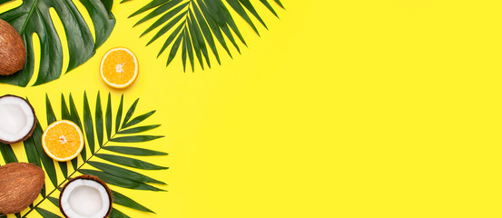 Summer tropical composition. Frame of Green tropical leaves of palm trees and monstera, coconut, orange on bright yellow background. Flat lay, top view, copy space. Creative background food, fruit