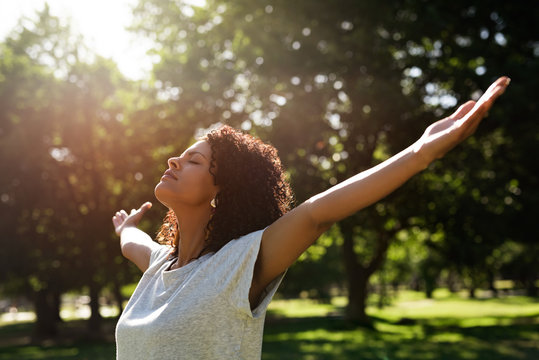Woman standing in a park rasing her arms skyward