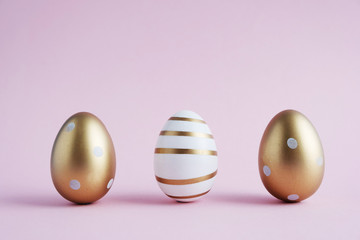 Three Easter eggs painted with gold paint in different patterns stand on a pink pastel color....