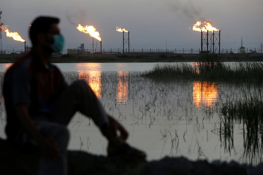 Flames emerge from flare stacks at Nahr Bin Umar oil field, as a man is seen wearing a protective face mask , following the outbreak of the coronavirus, north of Basra