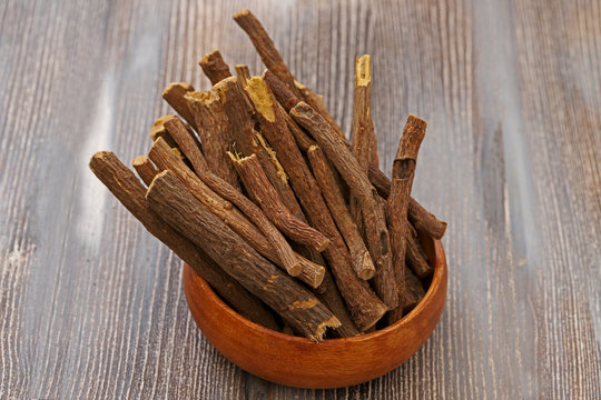 of a heap pile of Liquorice licorice roots sticks on a wooden board, its sweet fresh flavor can be extracted similar to star anise or fennel, used to flavor tobacco or to make rolled up candy