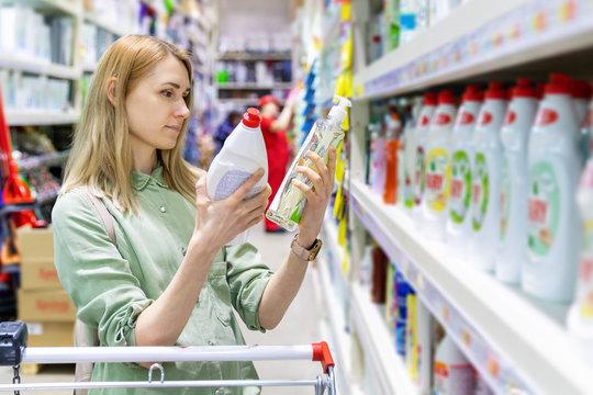 woman choosing detergents in household goods store