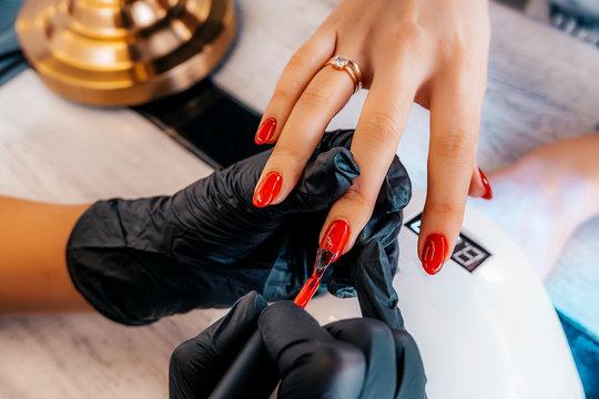 Red coating gel polish. Manicure gel polish for female nails.