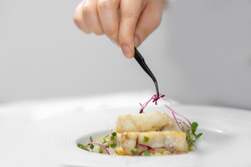 Chef with tweezers decorates with microgreens sprouts fish dish. Concept high art cooking, food decoration
