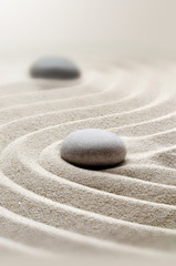 zen garden meditation stone background with stones and lines in sand for relaxation.