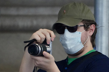A man wearing a mask to protect against coronavirus takes pictures at the New York Stock exchange (NYSE) in the Manhattan borough of New York City