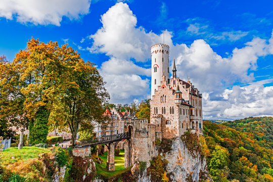 Germany, Lichtenstein Castle in Baden-Wurttemberg land in Swabian Alps. Seasonal view of Lichtenstein Castle on a cliff circled by trees with yellow foliage. European famous landmark.