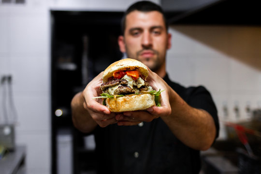 professional latin chef holding a prepared hamburger