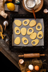 overhead shot of baked egg shaped easter cookies on baking tray on rustic wooden table with flour, eggs, butter, lemon. process of baking cookies. easter card