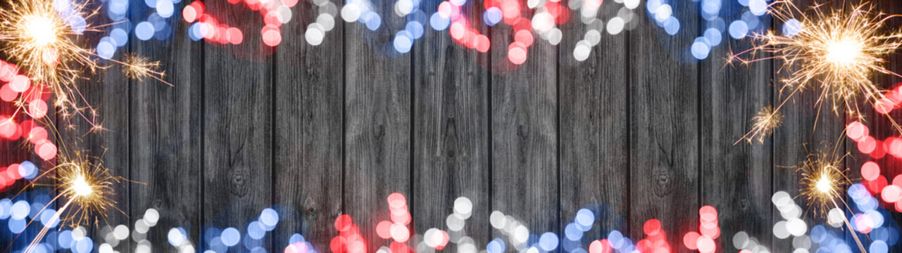Firework, sparklers and bokeh lights at night in the colors of the flag from the united states of america (blue, white and red)