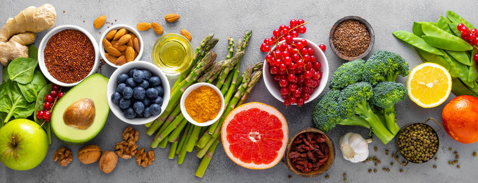 Healthy food background, spinach, quinoa, apple, blueberry, asparagus, turmeric, red currant, broccoli, mung bean, walnuts, grapefruit, ginger, avocado, almond, lemon  and green peas, top view, banner