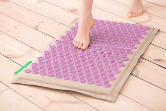Woman using acupressure mat at home..