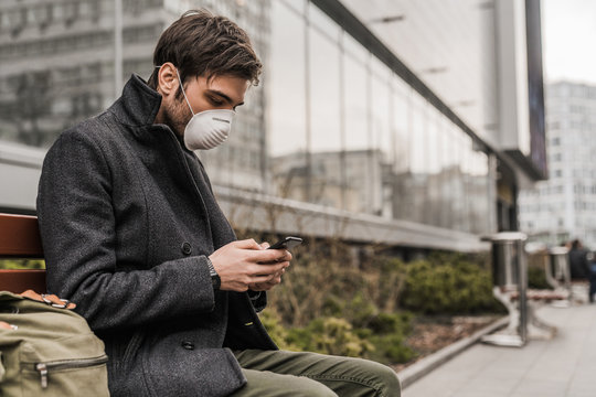 Man wears mask to prevent virus and for protection while using mobile phone