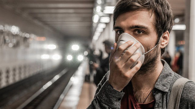 Young caucasian man in protection mask against virus at public subway station waiting for train