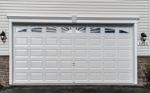 Double car classic insulated steel raised panel garage door framed with a white trim to add accent, with transom light windows divided by muntins on a new American home