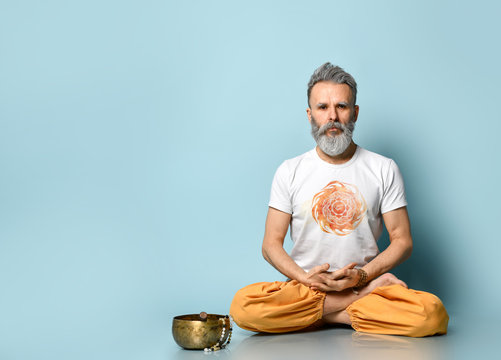 Yogi gray-haired man in dhoti clothes, holding rosary, sitting on floor in lotus pose on blue background. Singing bowl nearby