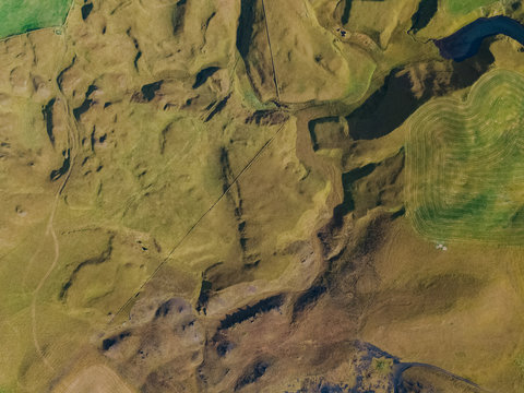 Iceland nature landscape texture background aerial top view from above. Amazing earth surface in Iceland at geothermal area. Drone aerial shot. Green and yellow grass from high.