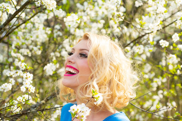 Happy smiling young woman with spring flowers at garden. Outdoor fashion photo of beautiful young woman surrounded by flowers. Spring blossom