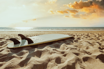 Wall Mural - Surfboard on beach background at sunset. Travel adventure and water sport.  retro color tone effect.