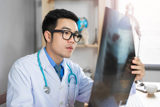 male asian medical doctor looking and examining a bone structure of an x-ray filter, holding the filter and diagnosing his patient health, wearing a lab coat stethoscope working in a hospital office