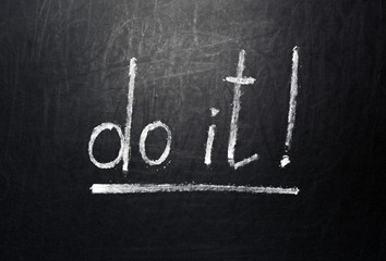 Handwritten motivation words - Do it! on the school chalkboard