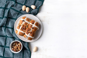 Delicious vegan homemade hot cross buns on a plate. The plate sits on a navy coloured tea towel and is surrounded by a bowl of various nuts and wooden easter eggs. Celebrate the Easter Holidays.