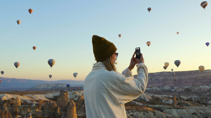 Young female taking pictures of air balloons by iphone Wall mural