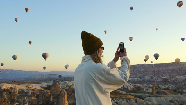 Young female taking pictures of air balloons by iphone
