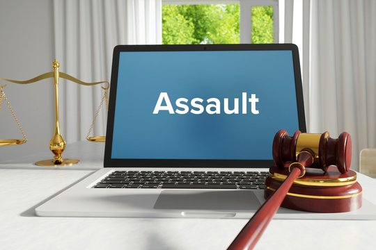 Assault – Law, Judgment, Web. Laptop in the office with term on the screen. Hammer, Libra, Lawyer.