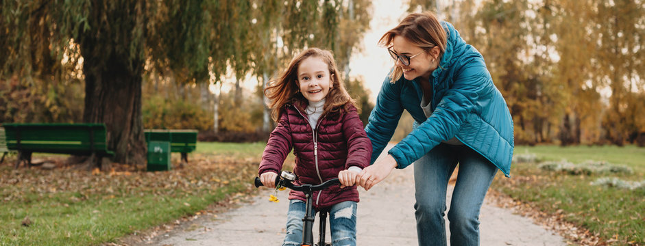 Cheerful middle aged woman is having joy with her girl while she is learning to ride the bike
