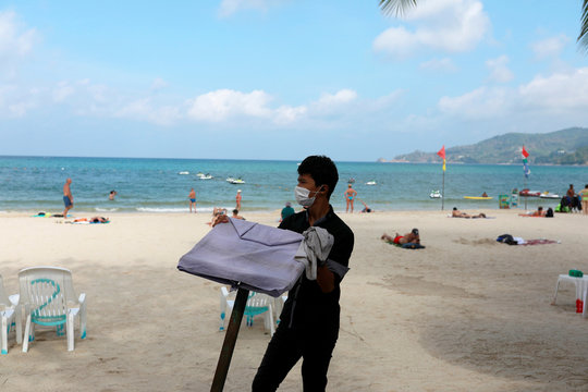 A waiter works in a beach with a few Western tourists, which is usually full of Chinese tourists, amid fear of coronavirus in Phuket