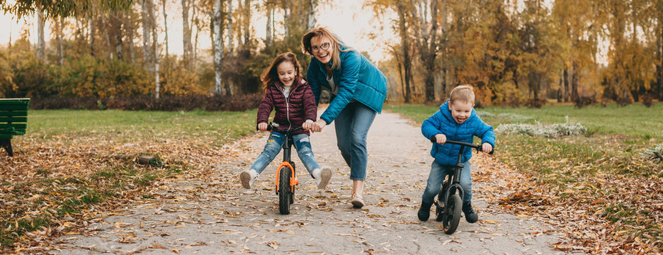 Smiling caucasian mother is playing with her small kids while teaching them to ride the bike