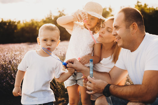 Charming caucasian family posing in a lavender field while making balloons together