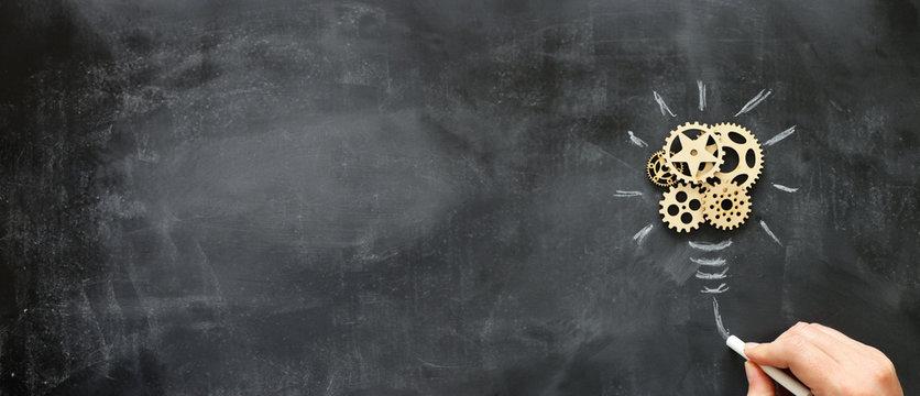Education concept image. Creative idea and innovation. Wooden gears light bulb metaphor over blackboard