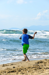 boy throwing sand to the waves on a beach