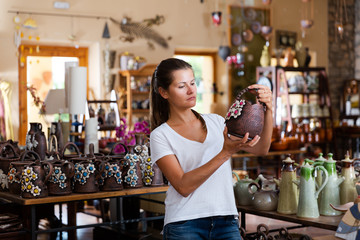 Female buyer chooses ceramic dishes and decorative items in a store