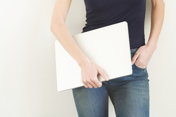 Young student holding laptop against gray wall