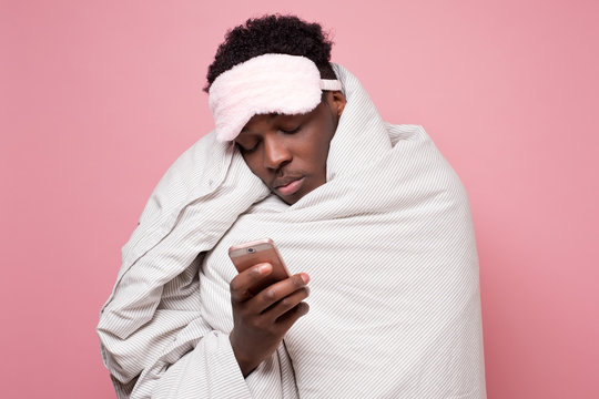 Tired young black man is awaked by the phone conversation at night. Annoying spam call concept
