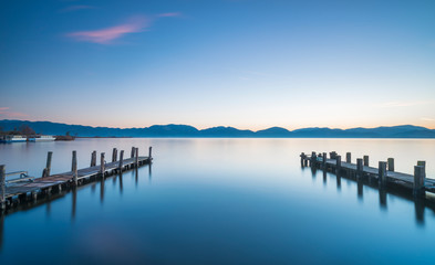 Two Wooden pier or jetty at sunset and sky reflection on water. Versilia Tuscany, Italy Fotomurales