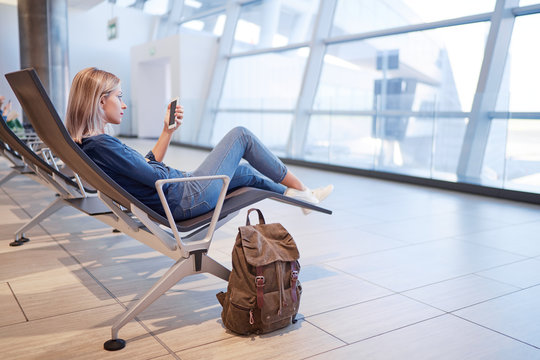 Travel and technology. Pretty young woman using smartphone while sitting at airport terminal waiting for boarding.