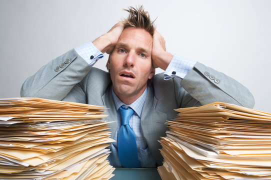 Fatigued office worker holding his head in his hands on the piles of file folders on his desk