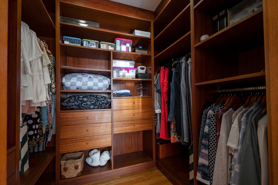 Modern wooden wardrobe with clothes hanging on rail in walk in closet.