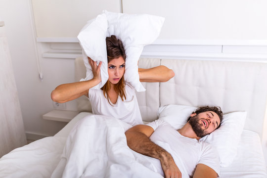 Man snoring while his wife is covering ears with pillow. Woman suffers from her male partner snoring in bed. Noise concept. Real people. Young irritated woman lying in bed with snoring husband