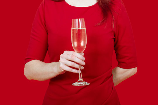 close up of a woman dressed in red holding a flute of bubbles prosecco champagne aperitif festivity party elegance on red background