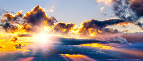 dramatic sunset sky landscape background natural color of evening cloudscape panorama with setting sun rays coming through clouds wide panoramic view Fotomurales